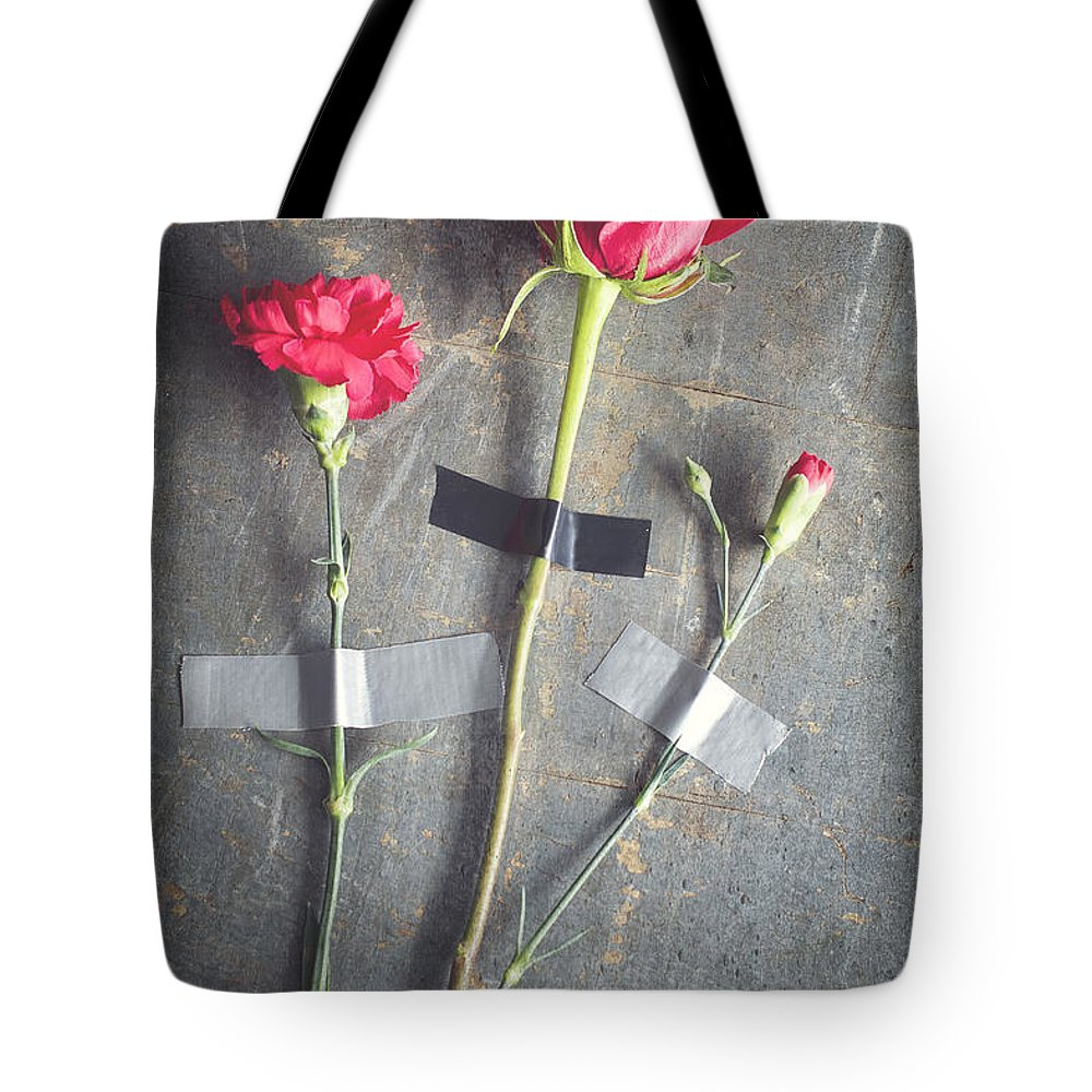 Three Tote Bag featuring the photograph Three Red Flowers Taped To Wooden Background by Di Kerpan