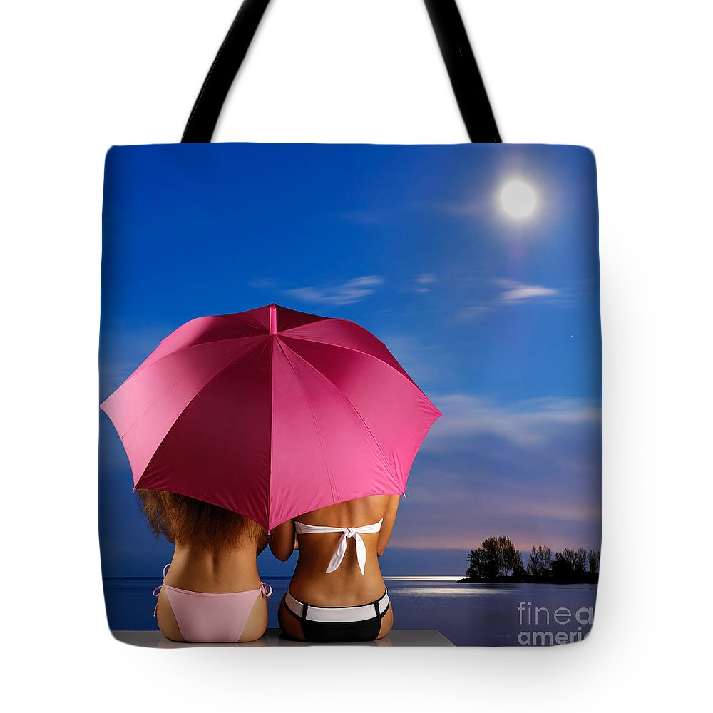 Beach Tote Bag featuring the photograph Two Women Relaxing On A Shore by Oleksiy Maksymenko