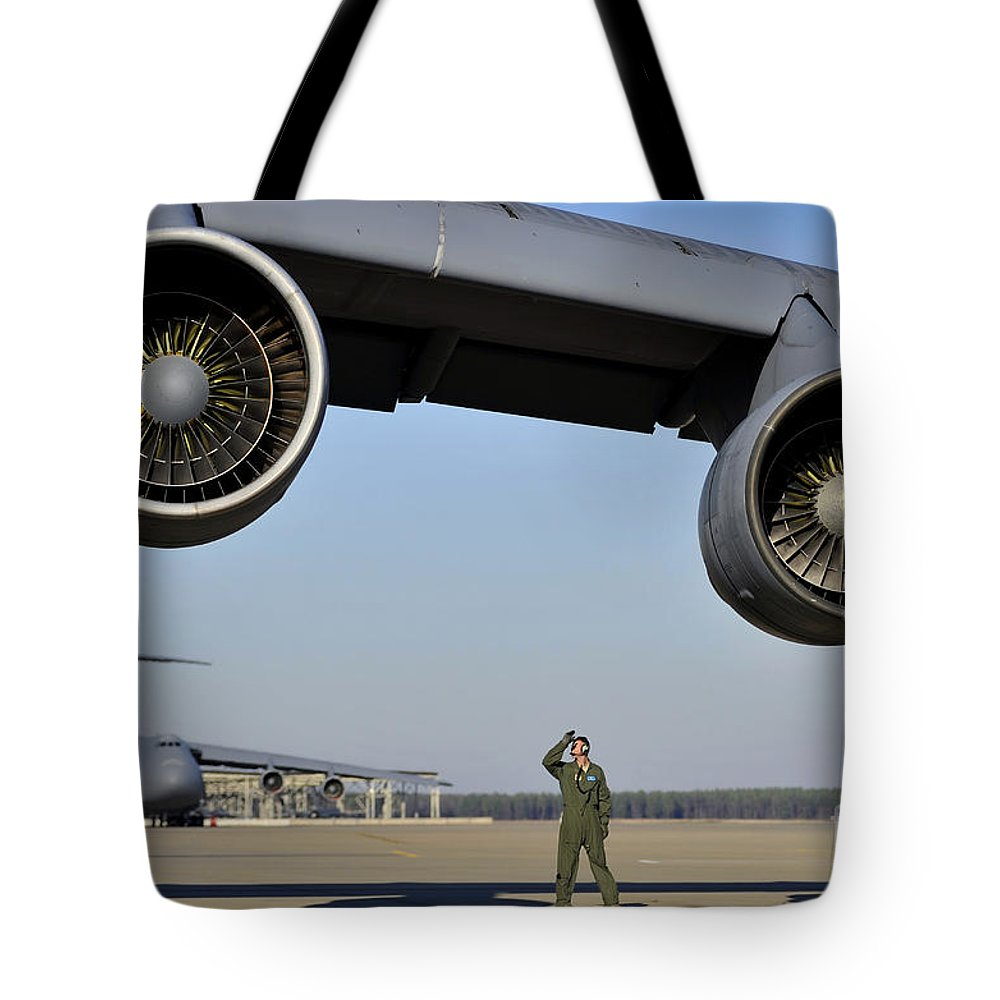 Us Air Force Tote Bag featuring the photograph U.s. Air Force Crew Chief Performs by Stocktrek Images