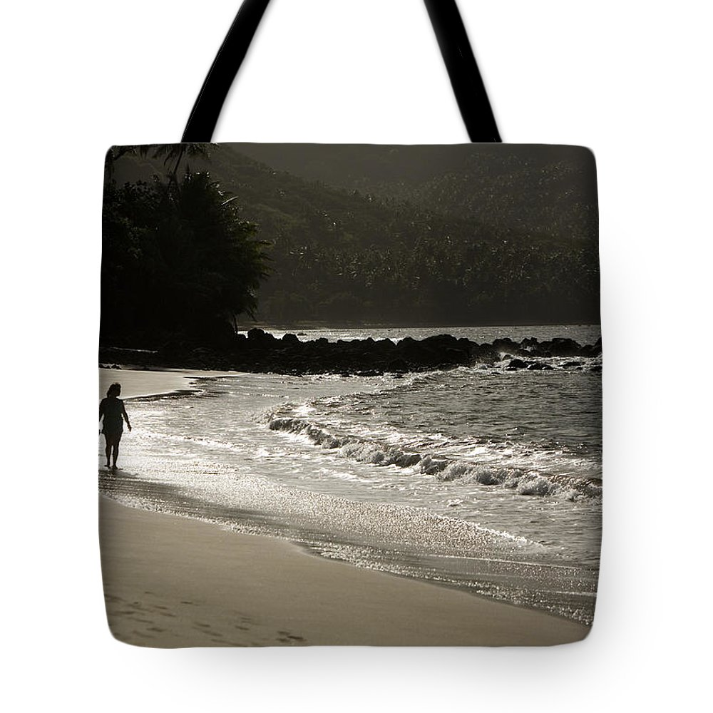 One Mid Adult Woman Tote Bag featuring the photograph Woman Walking On A Deserted Beach by Tim Laman