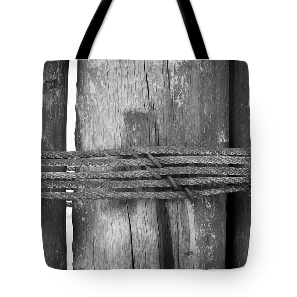 Isolated Tote Bag featuring the photograph Wood Pilings Tied With Old Rusted Rope by Mina Fouad