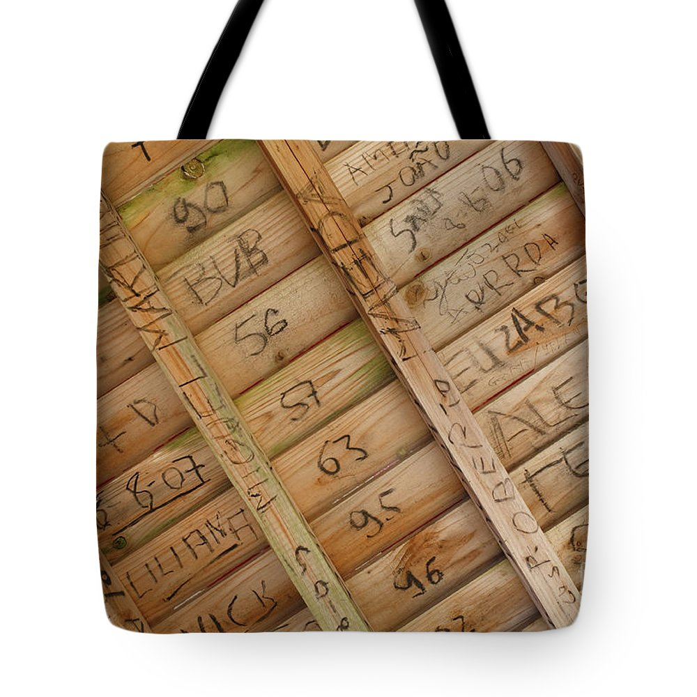 Writing Tote Bag featuring the photograph Writings On Wood by Gaspar Avila