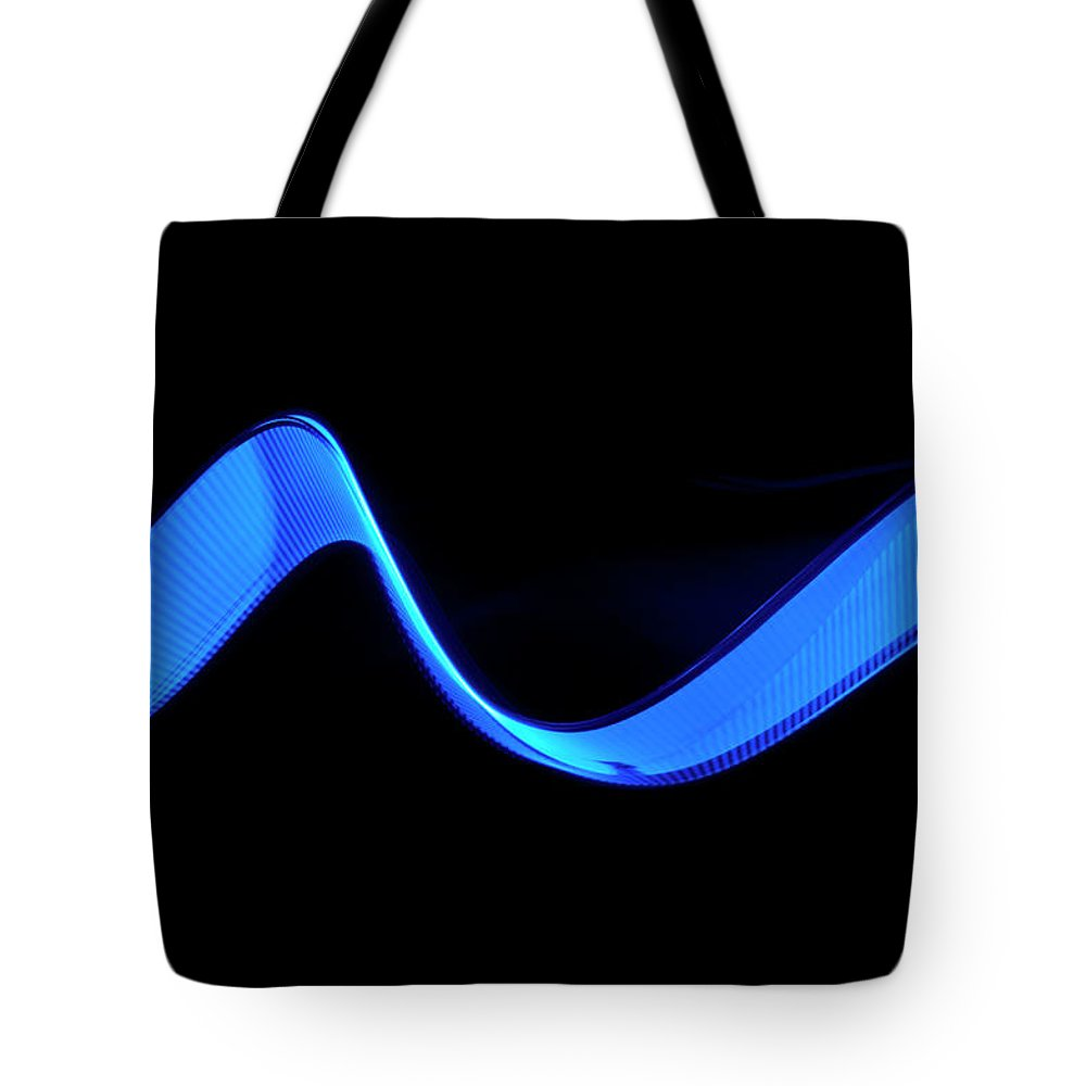 Laser Tote Bag featuring the photograph Blue Abstract Coloured Lights Trails by John Rensten