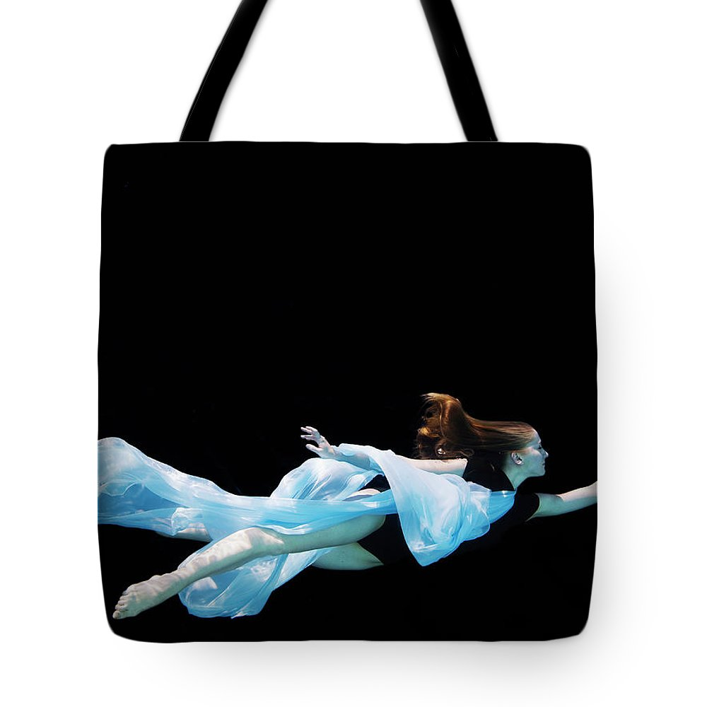 Ballet Dancer Tote Bag featuring the photograph Female Dancer Underwater Against Black by Thomas Barwick
