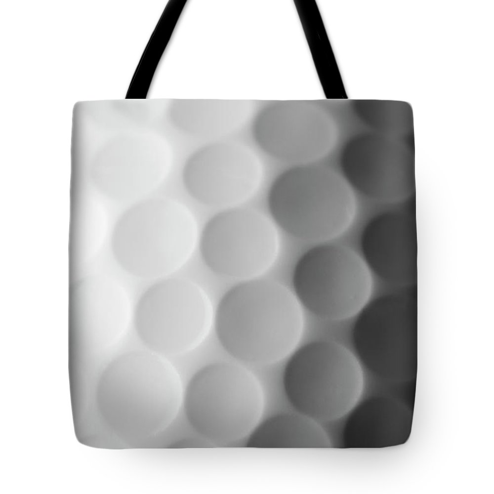 Ball Tote Bag featuring the photograph A Close Up Shot Of A Golf Ball, White by Anthiacumming