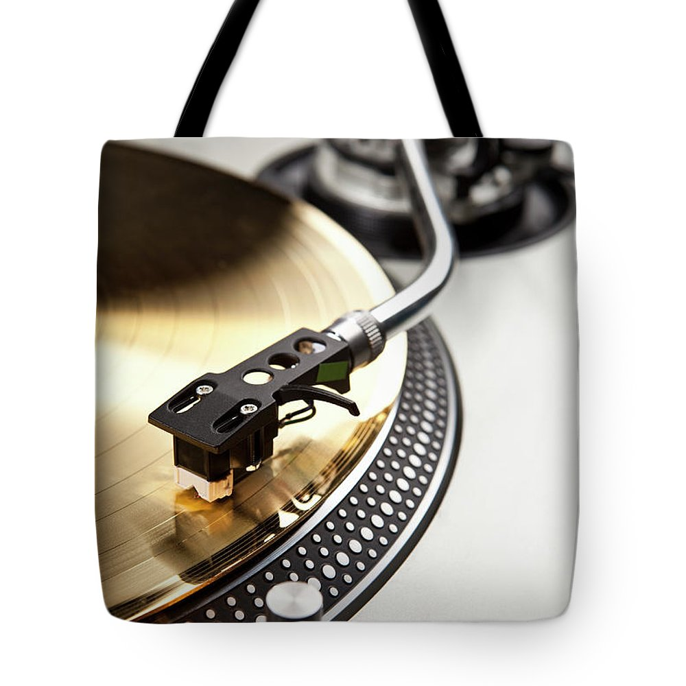 Music Tote Bag featuring the photograph A Gold Record On A Turntable by Caspar Benson