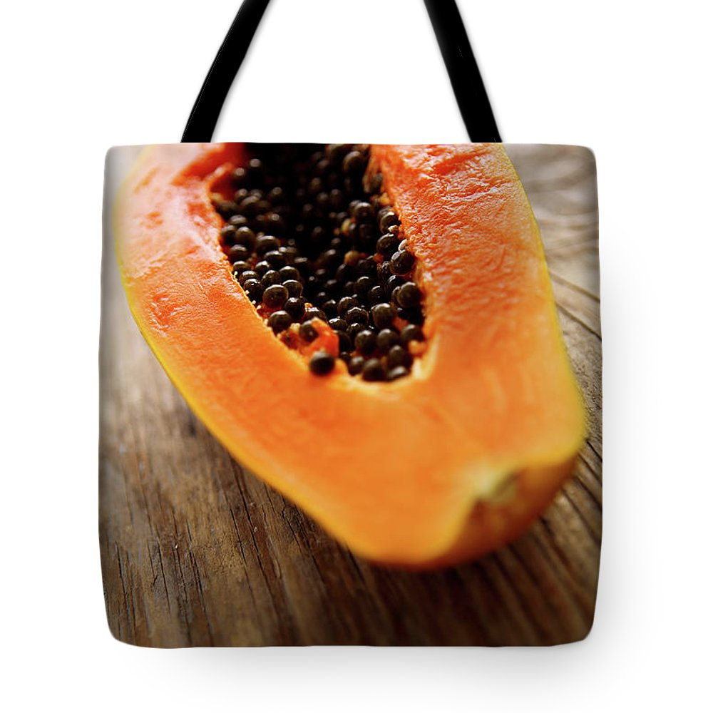 Serving Size Tote Bag featuring the photograph A Halved Fresh Papaya On A Wooden by Chang