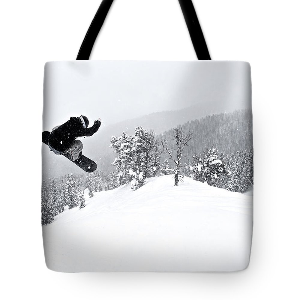 Recreational Pursuit Tote Bag featuring the photograph A Man On A Snowboard Flies Through The by Derek Diluzio