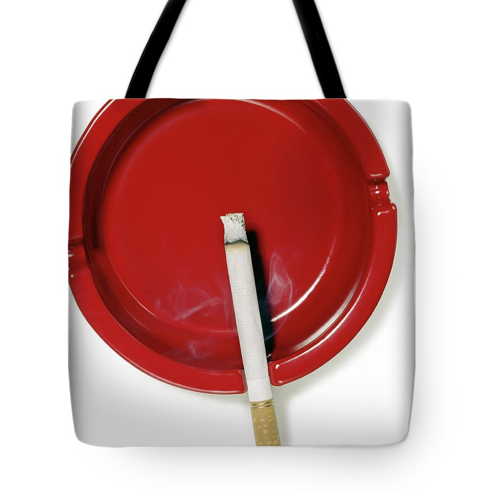 White Background Tote Bag featuring the photograph A Red Ashtray With A Burning Cigarette by Steve Wisbauer