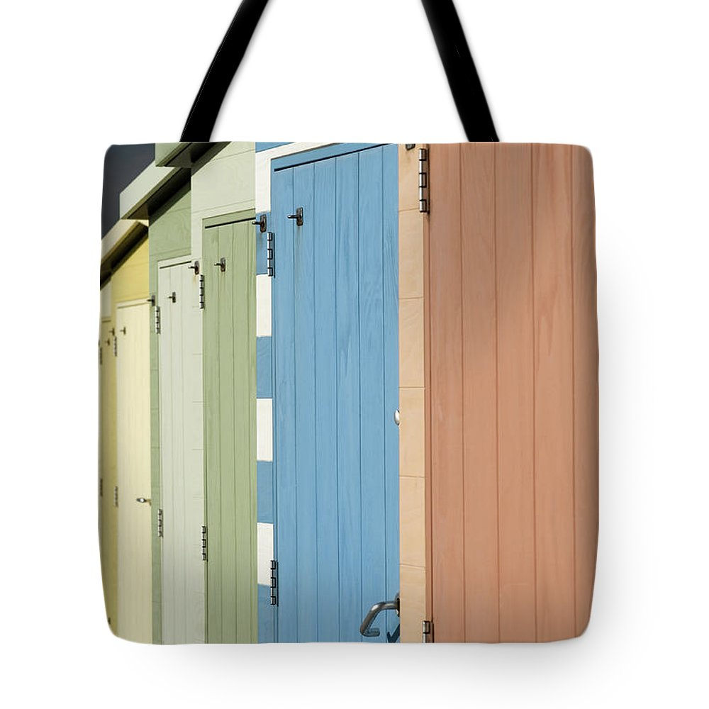 Beach Hut Tote Bag featuring the photograph A Row Of Beach Huts by Matthew Piper