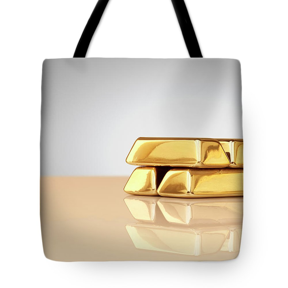 Four Objects Tote Bag featuring the photograph A Stack Of Four Gold Ingots by Anthony Bradshaw
