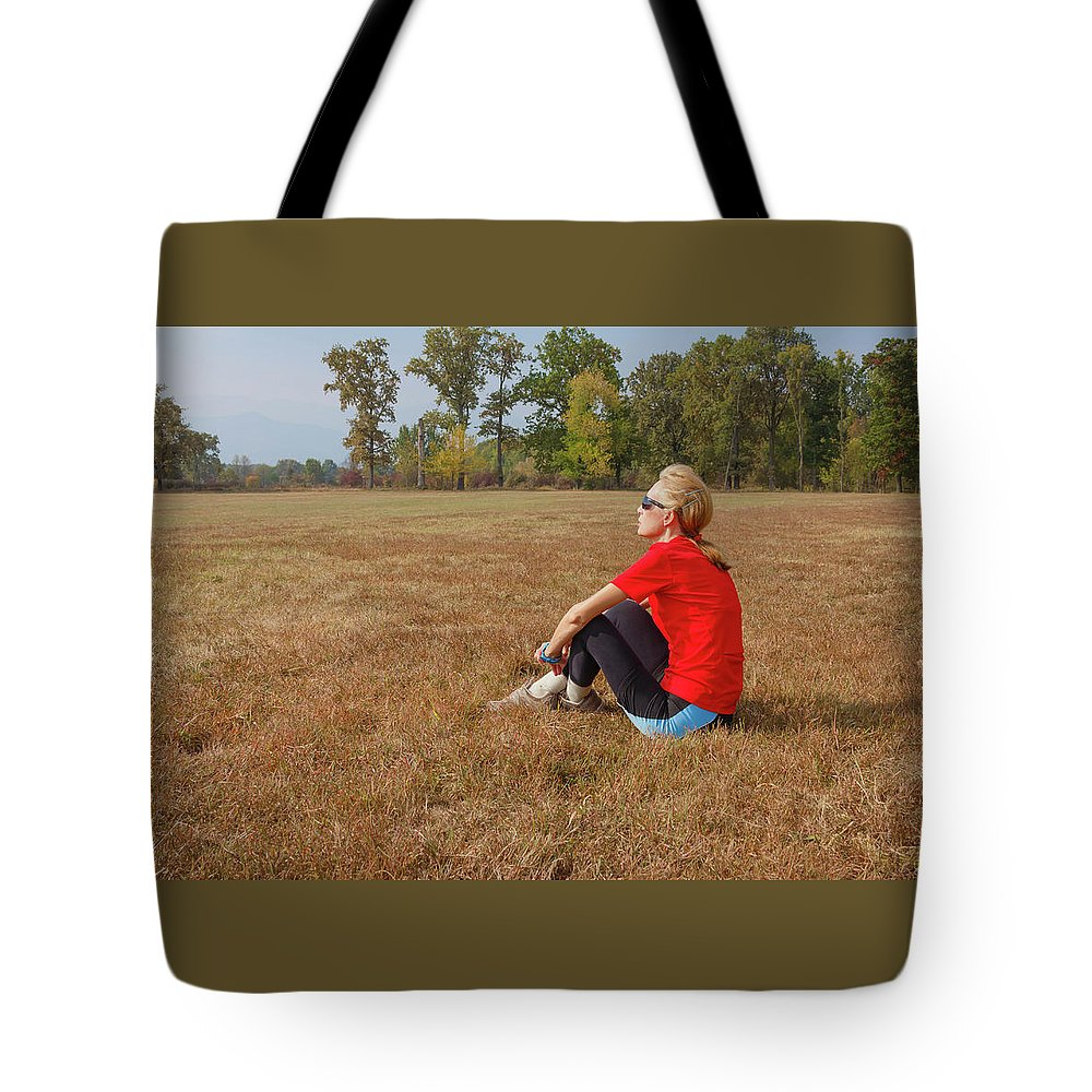 Admire Tote Bag featuring the photograph A Woman Is Sitting In A Park And Admiring The Landscape by Daniele Mattioda