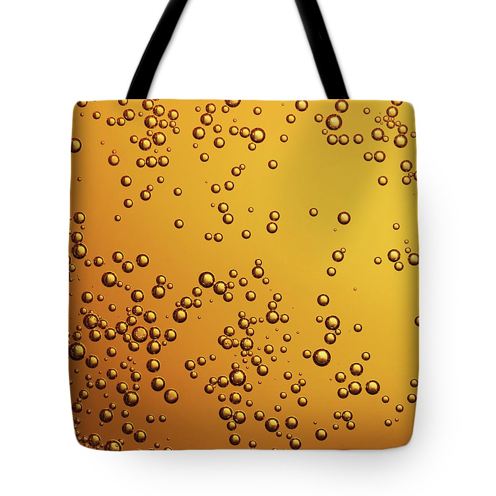 Alcohol Tote Bag featuring the photograph Amber Colored Carbonated Bubbles by Burwellphotography