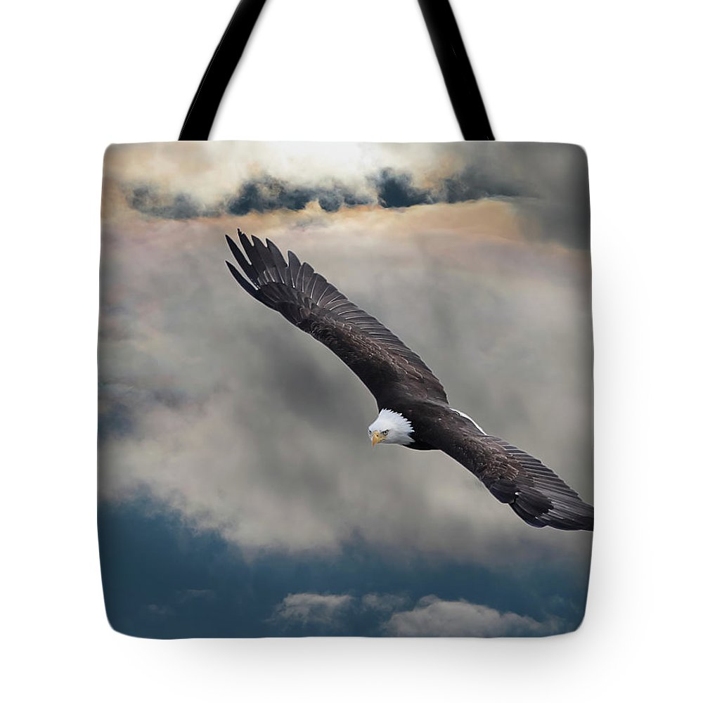 Bird Of Prey Tote Bag featuring the photograph An Eagle In Flight Rising Above The by Design Pics / Robert Bartow