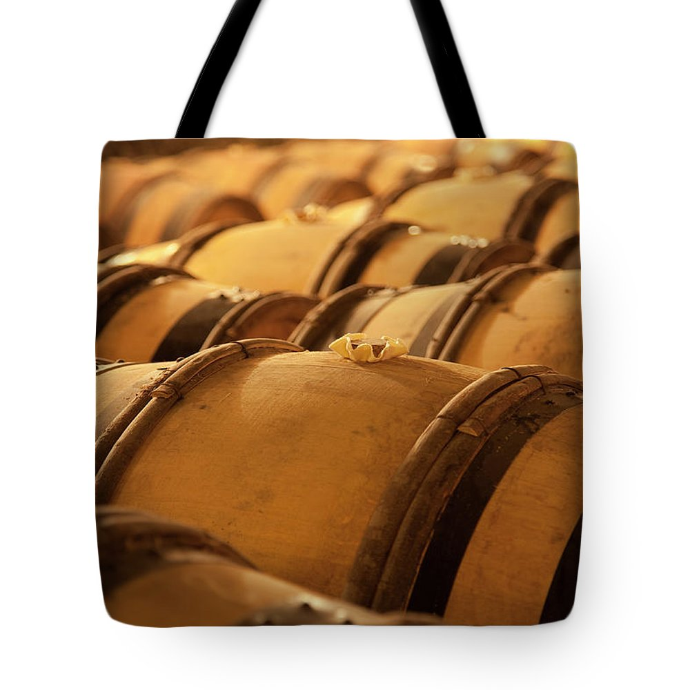 Fermenting Tote Bag featuring the photograph An Old Wine Cellar Full Of Barrels by Brasil2