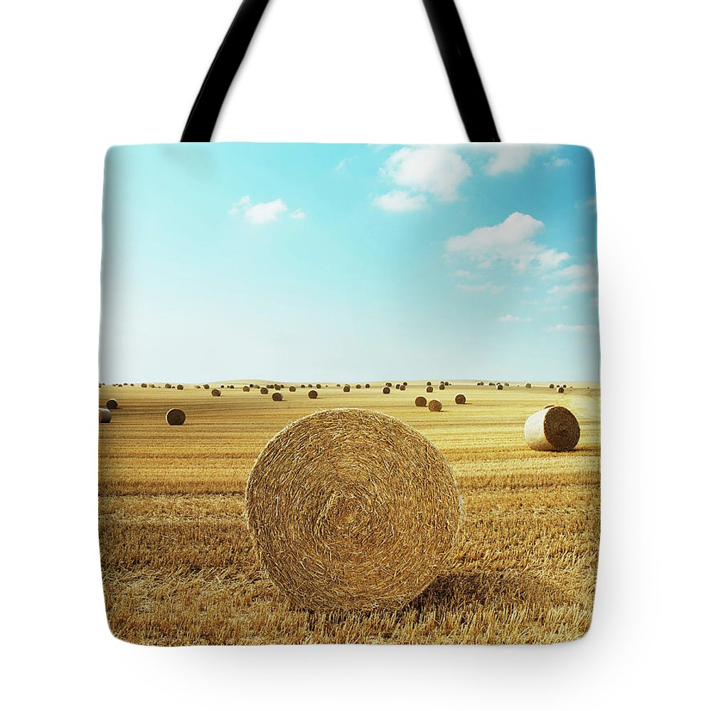 Field Stubble Tote Bag featuring the photograph Bales Of Hay In Harvested Field by Henrik Sorensen