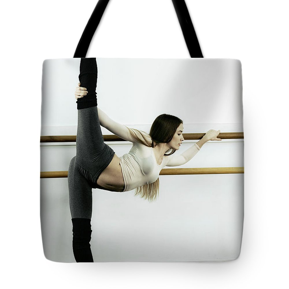 Ballet Dancer Tote Bag featuring the photograph Ballet Dancer Stretching In Dance by Patrik Giardino