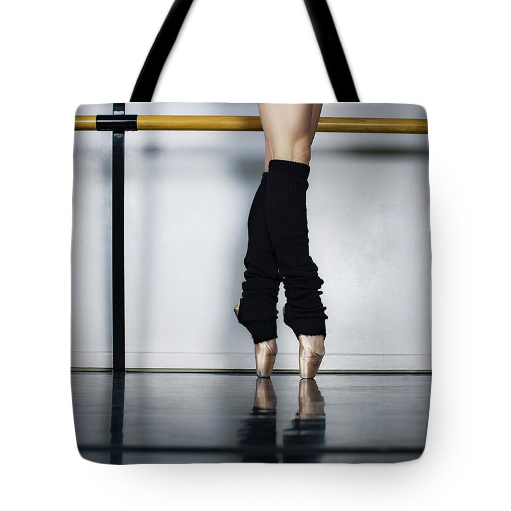 Ballet Dancer Tote Bag featuring the photograph Ballet Holdiing Bar In Classic Pointe by Patrik Giardino