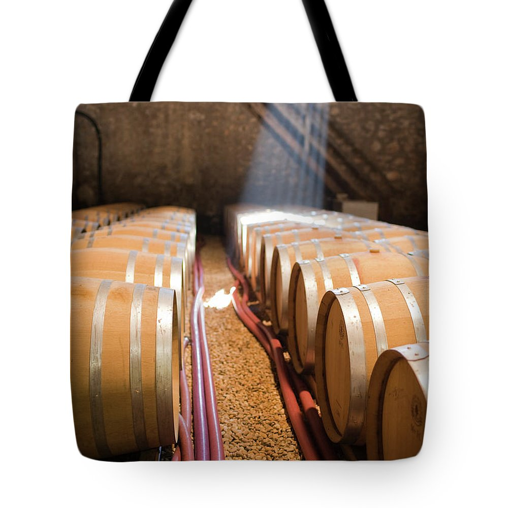 Alcohol Tote Bag featuring the photograph Barrels In Wine Cellar by Johner Images
