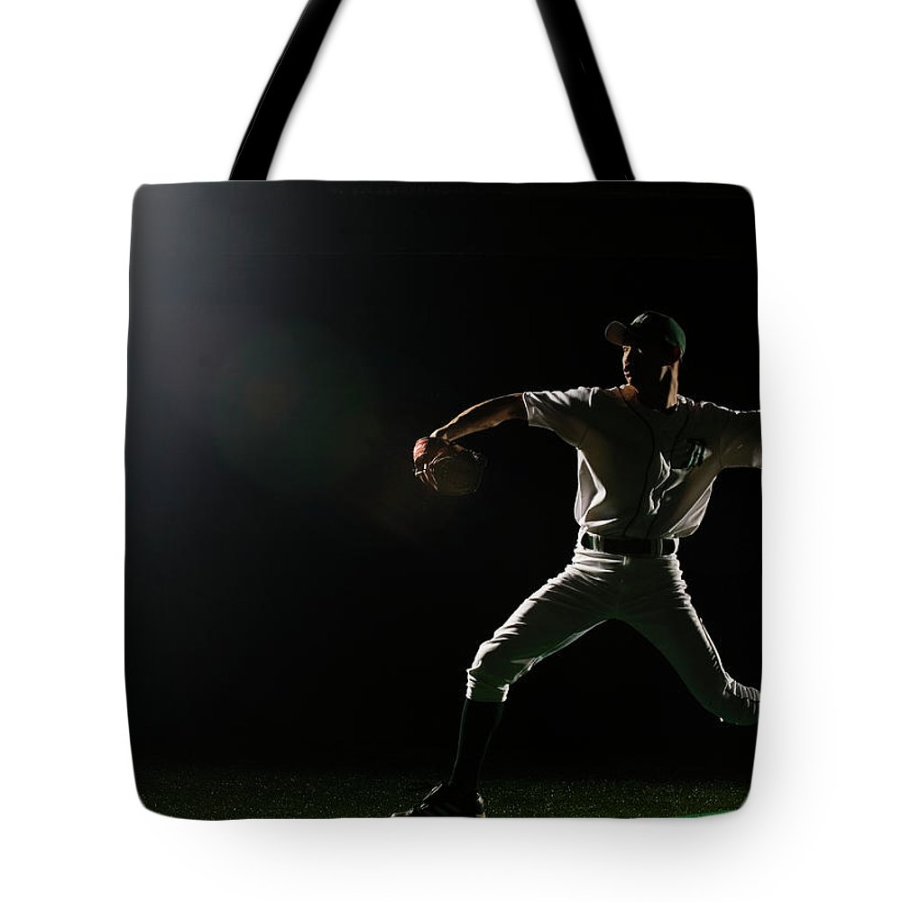 Human Arm Tote Bag featuring the photograph Baseball Pitcher Releasing Ball by Pm Images