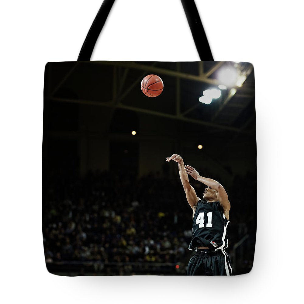 Expertise Tote Bag featuring the photograph Basketball Player Shooting Jump Shot In by Thomas Barwick