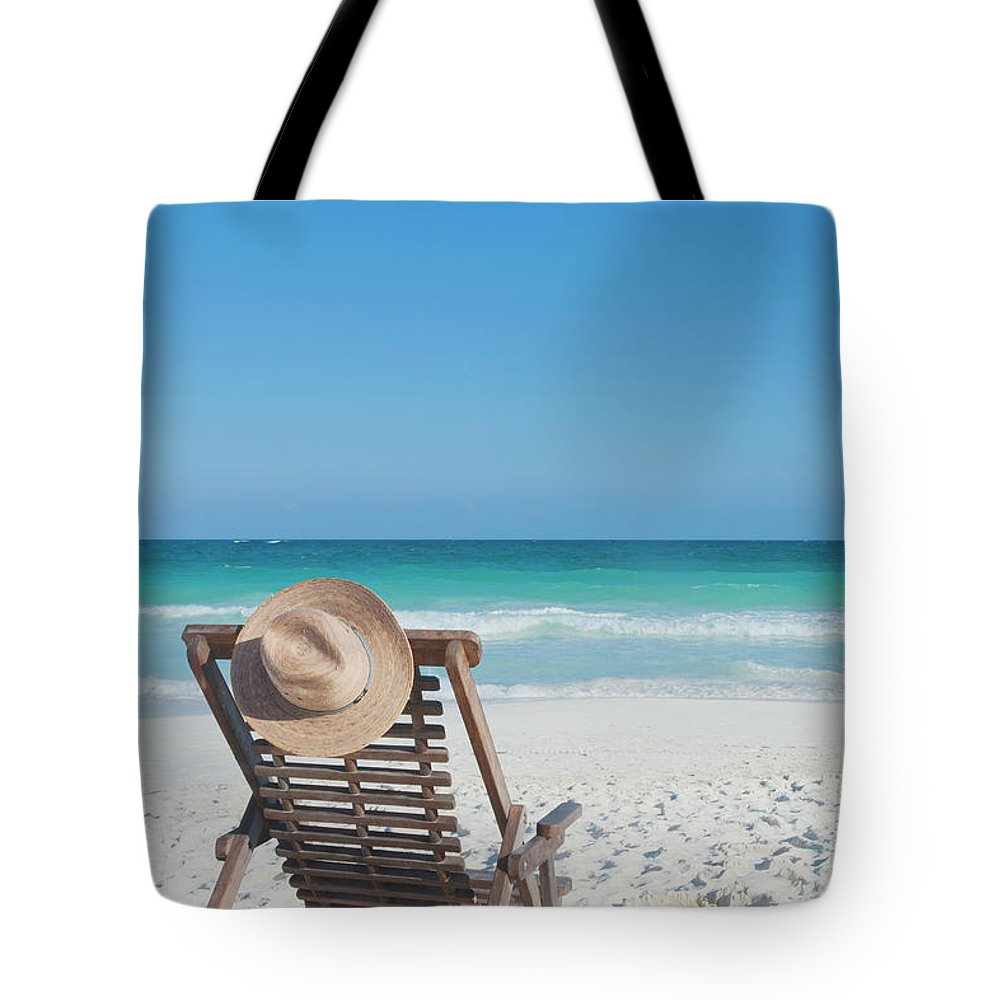 Scenics Tote Bag featuring the photograph Beach Chair With A Hat On An Empty Beach by Sasha Weleber