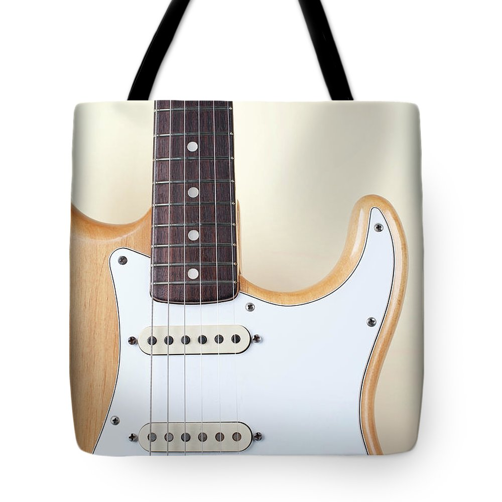 Rock Music Tote Bag featuring the photograph Beige Wood Textured Electric Guitar by Neyya