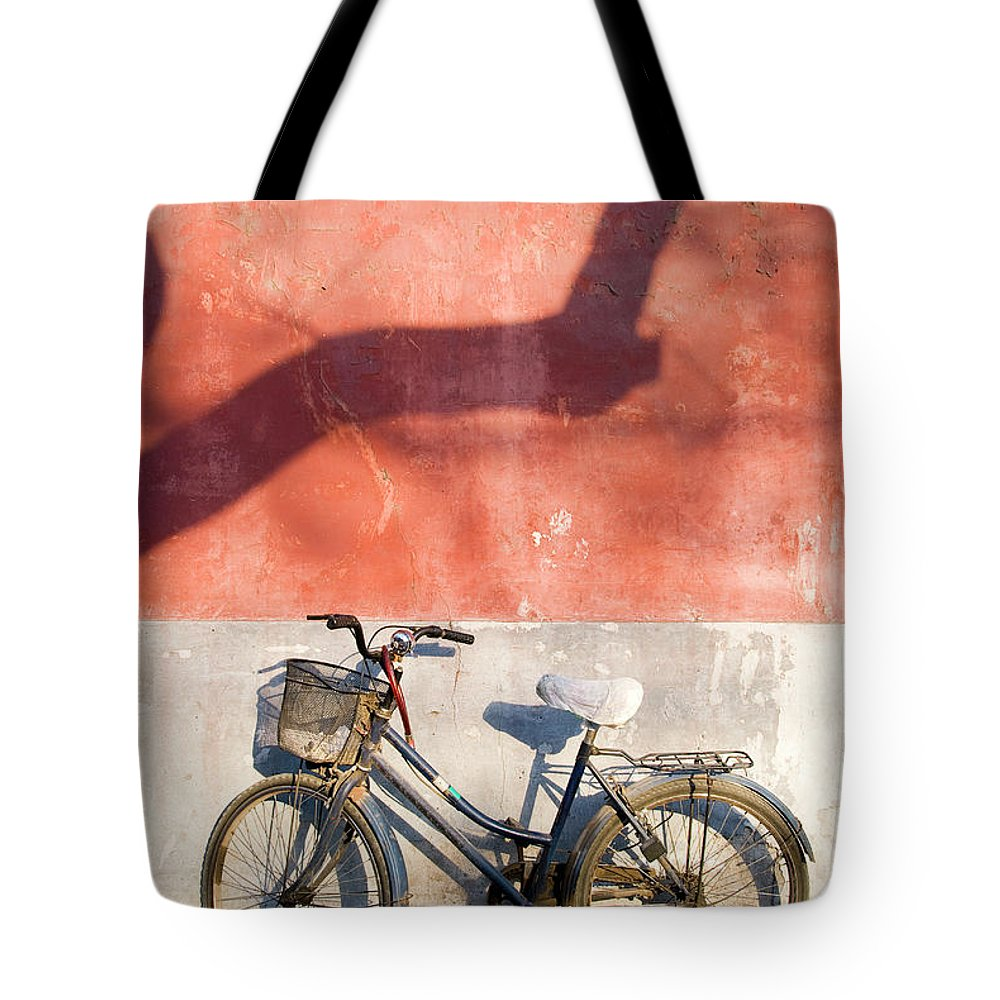 Chinese Culture Tote Bag featuring the photograph Bicycle Against Red Wall by Frankvandenbergh