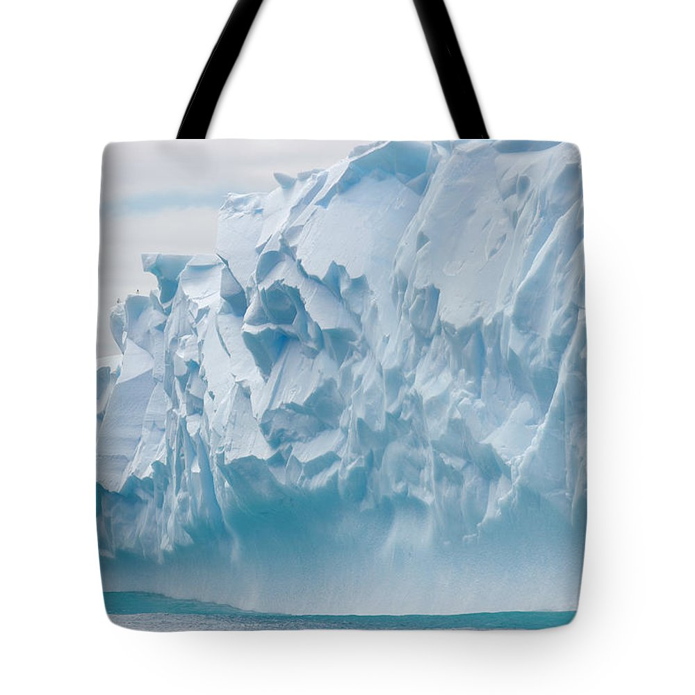 Scenics Tote Bag featuring the photograph Blue Iceberg Carved By Waves Floats In by Eastcott Momatiuk