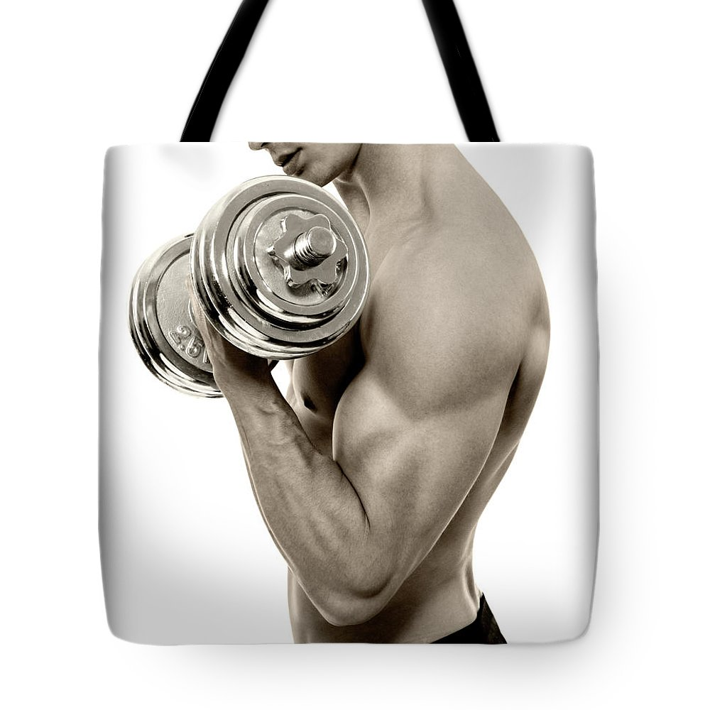 Young Men Tote Bag featuring the photograph Body Builder Exercising by Gilaxia