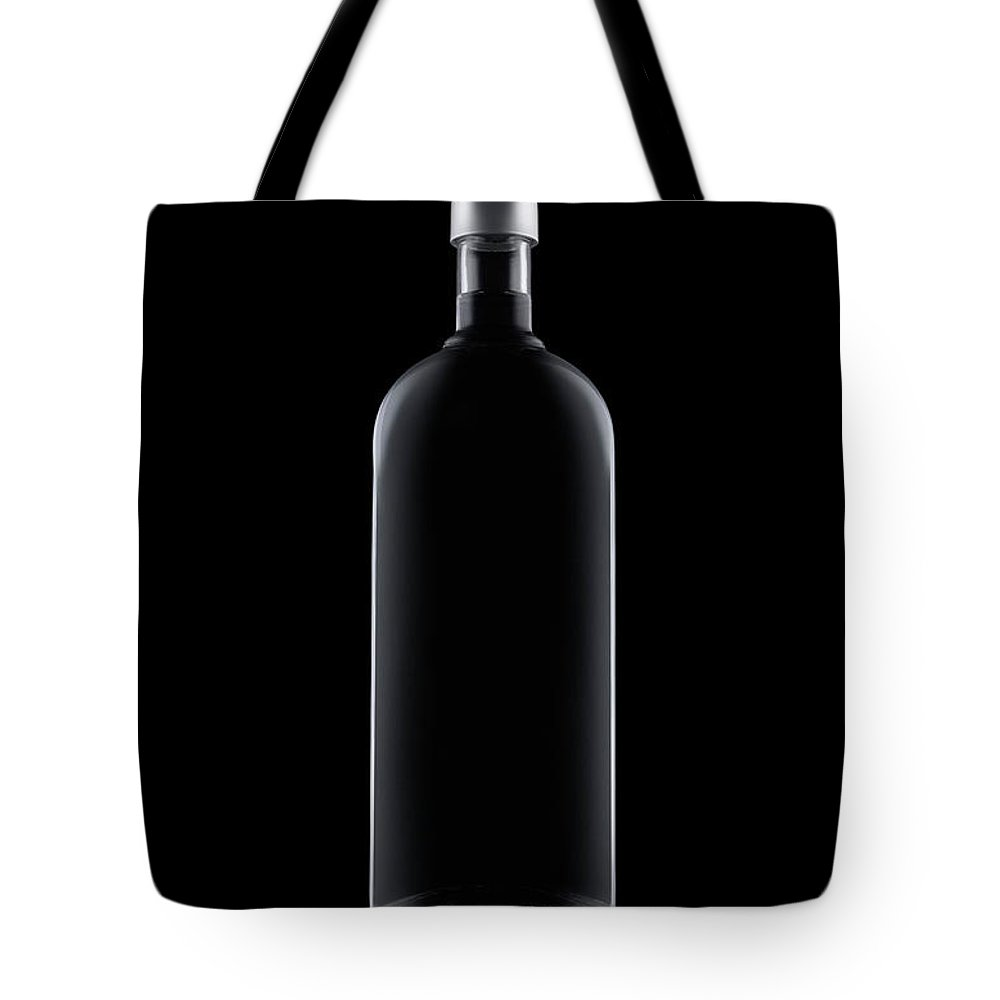 Black Color Tote Bag featuring the photograph Bottle Of Water Isolated On Black by Kedsanee