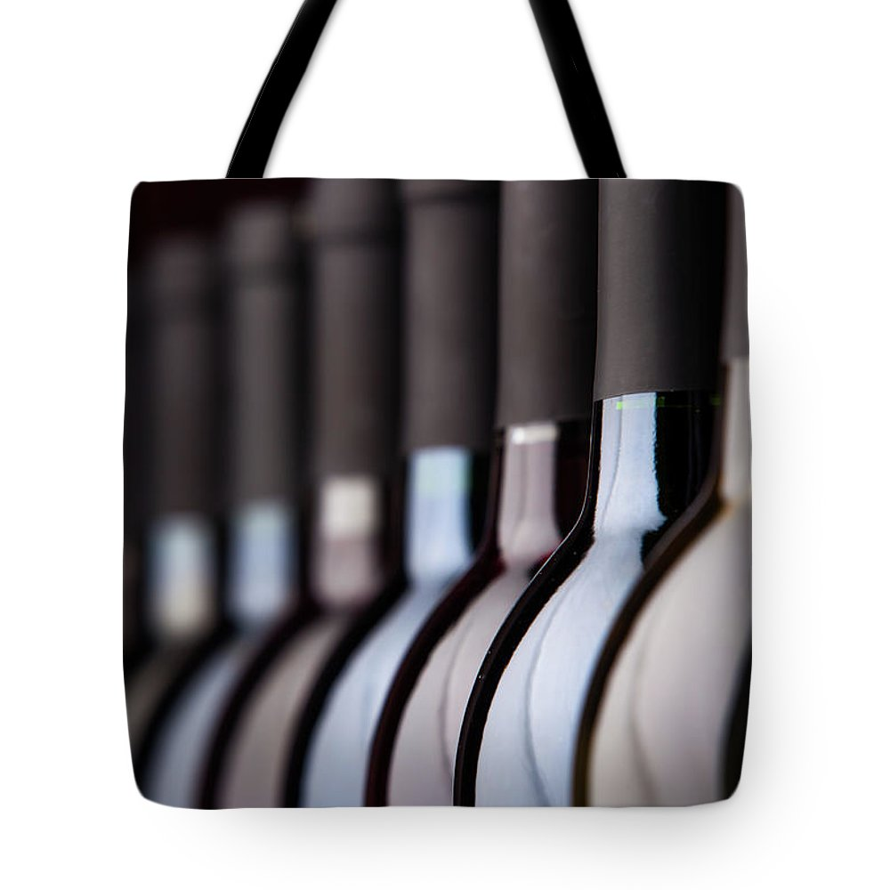 Alcohol Tote Bag featuring the photograph Bottles Of Wine In A Row by Halbergman
