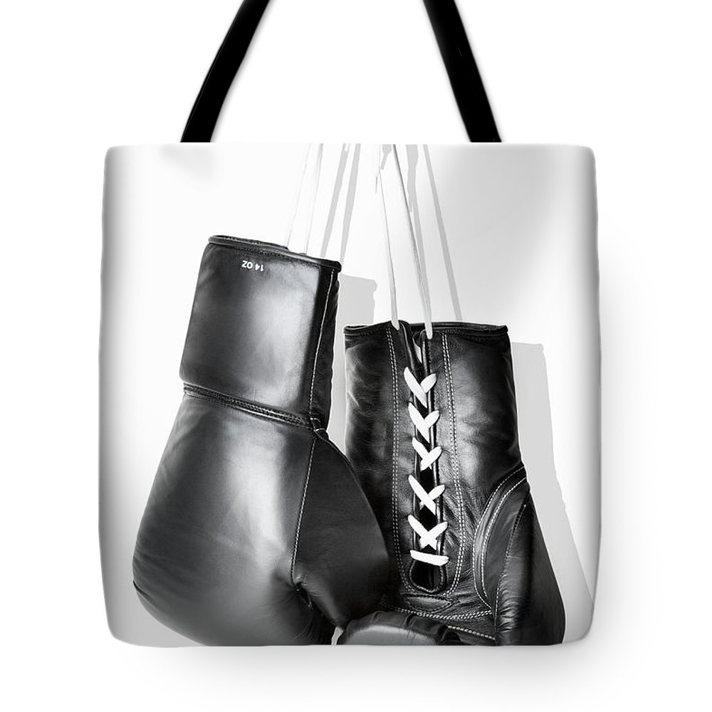 Hanging Tote Bag featuring the photograph Boxing Gloves Hanging Against White by Burazin