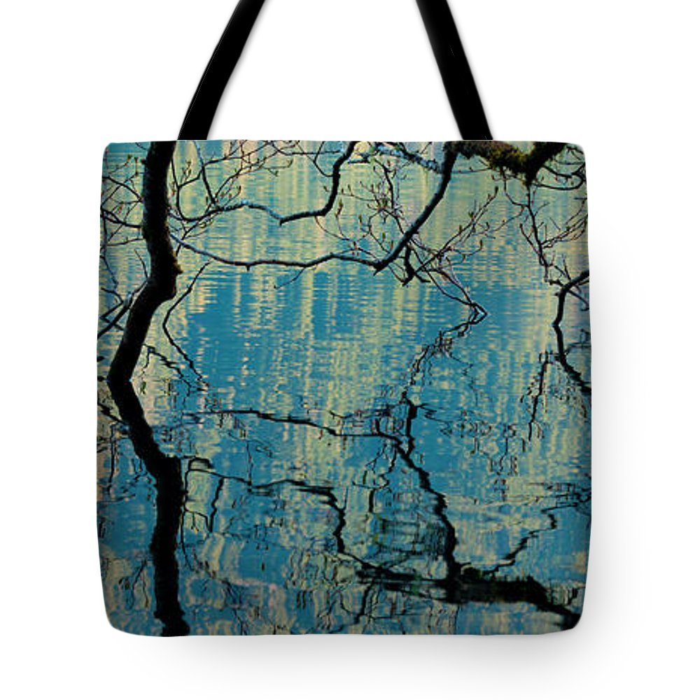 Tranquility Tote Bag featuring the photograph Branches Dip Into The Surface Of Lake by Mint Images/ Art Wolfe