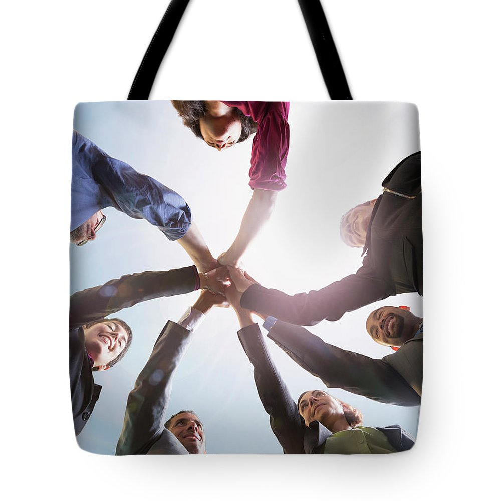 Working Tote Bag featuring the photograph Business People Putting Hands Together by John M Lund Photography Inc