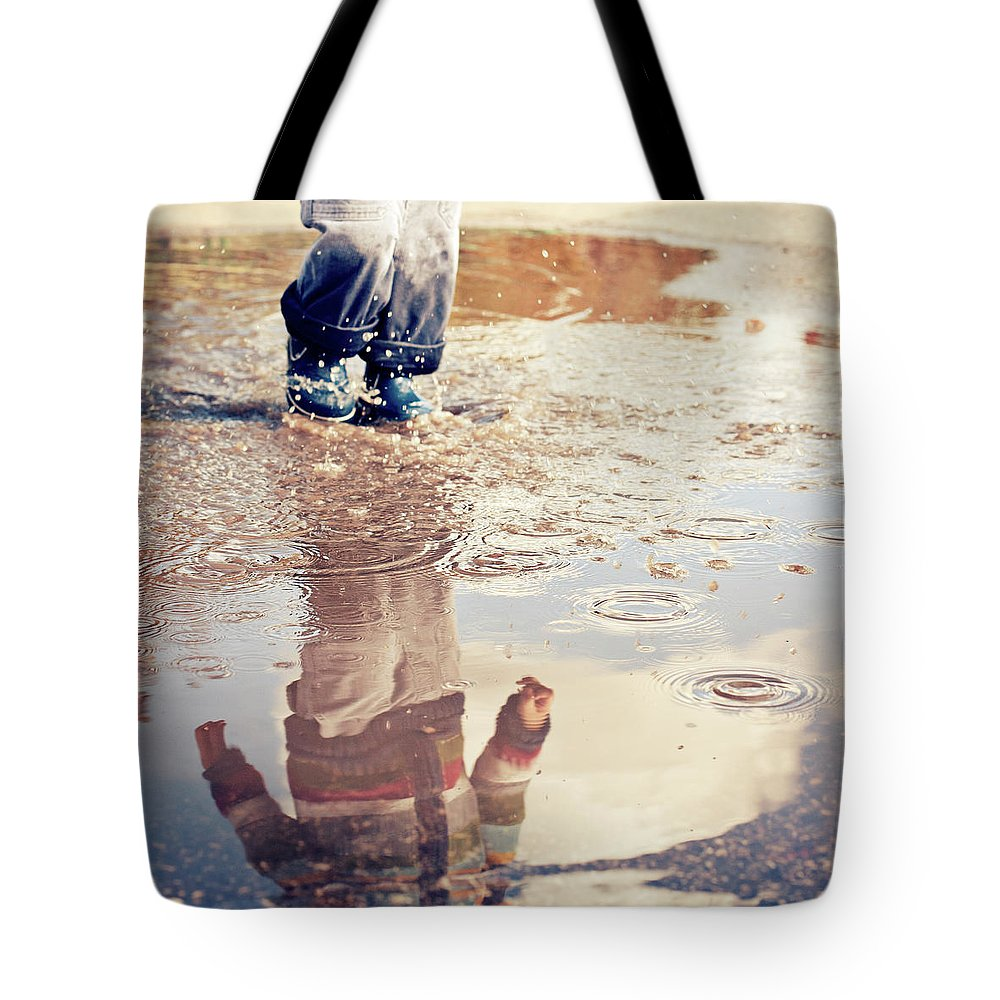 Toddler Tote Bag featuring the photograph Child In A Puddle by Vpopovic
