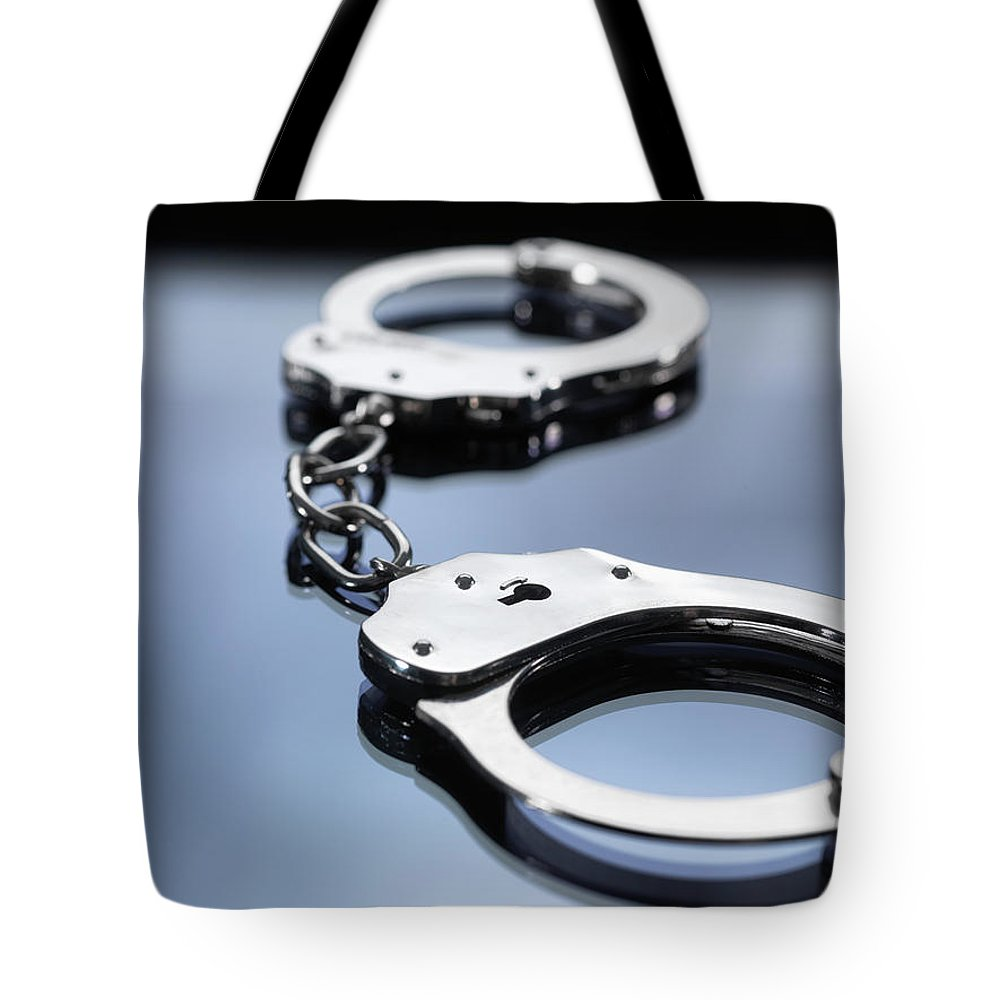 Punishment Tote Bag featuring the photograph Close Up Of Metal Handcuffs by Andrew Brookes