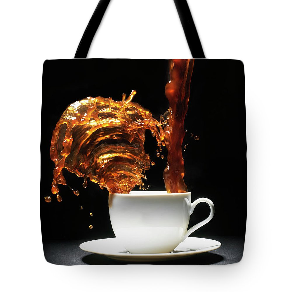 Black Background Tote Bag featuring the photograph Coffee Being Poured Into Cup Splashing by Henrik Sorensen