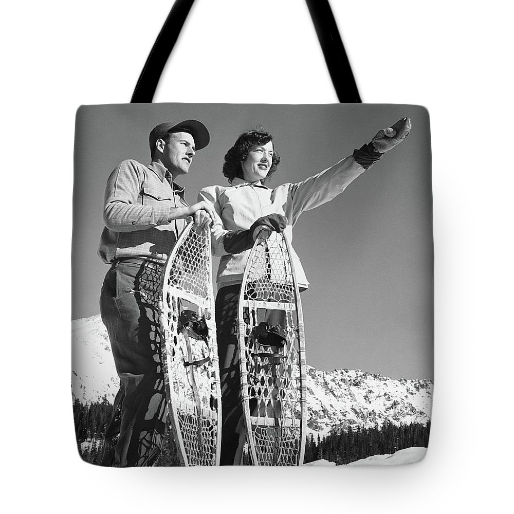 Heterosexual Couple Tote Bag featuring the photograph Couple Holding Snowshoes, Woman Pointing by Stockbyte