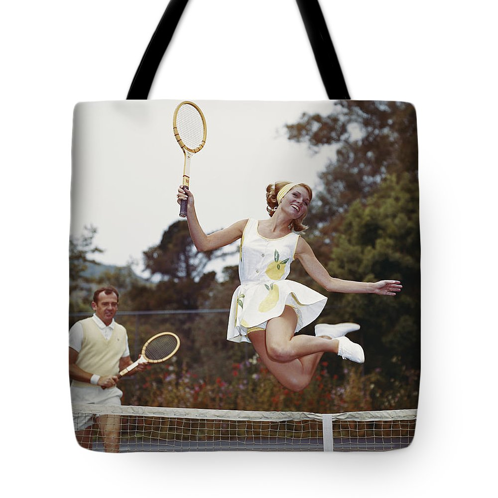 Heterosexual Couple Tote Bag featuring the photograph Couple On Tennis Court, Woman Jumping by Tom Kelley Archive