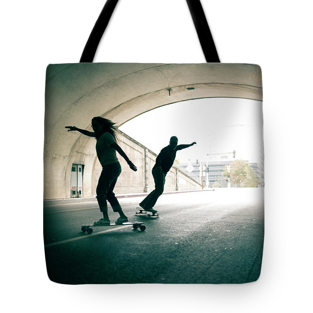 Mature Adult Tote Bag featuring the photograph Couple Skateboarding Through Tunnel by Ian Logan