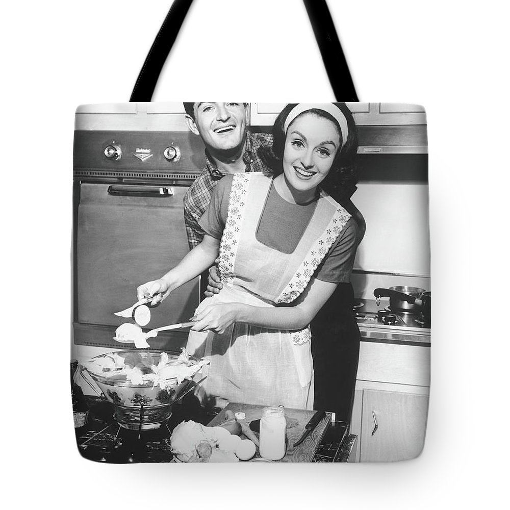 Heterosexual Couple Tote Bag featuring the photograph Couple Standing In Kitchen, Smiling, B&w by George Marks