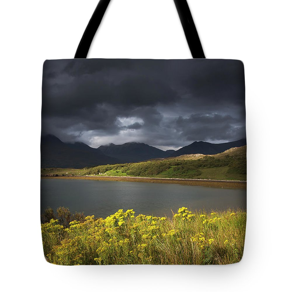 Tranquility Tote Bag featuring the photograph Dark Storm Clouds Hang Over The by John Short / Design Pics