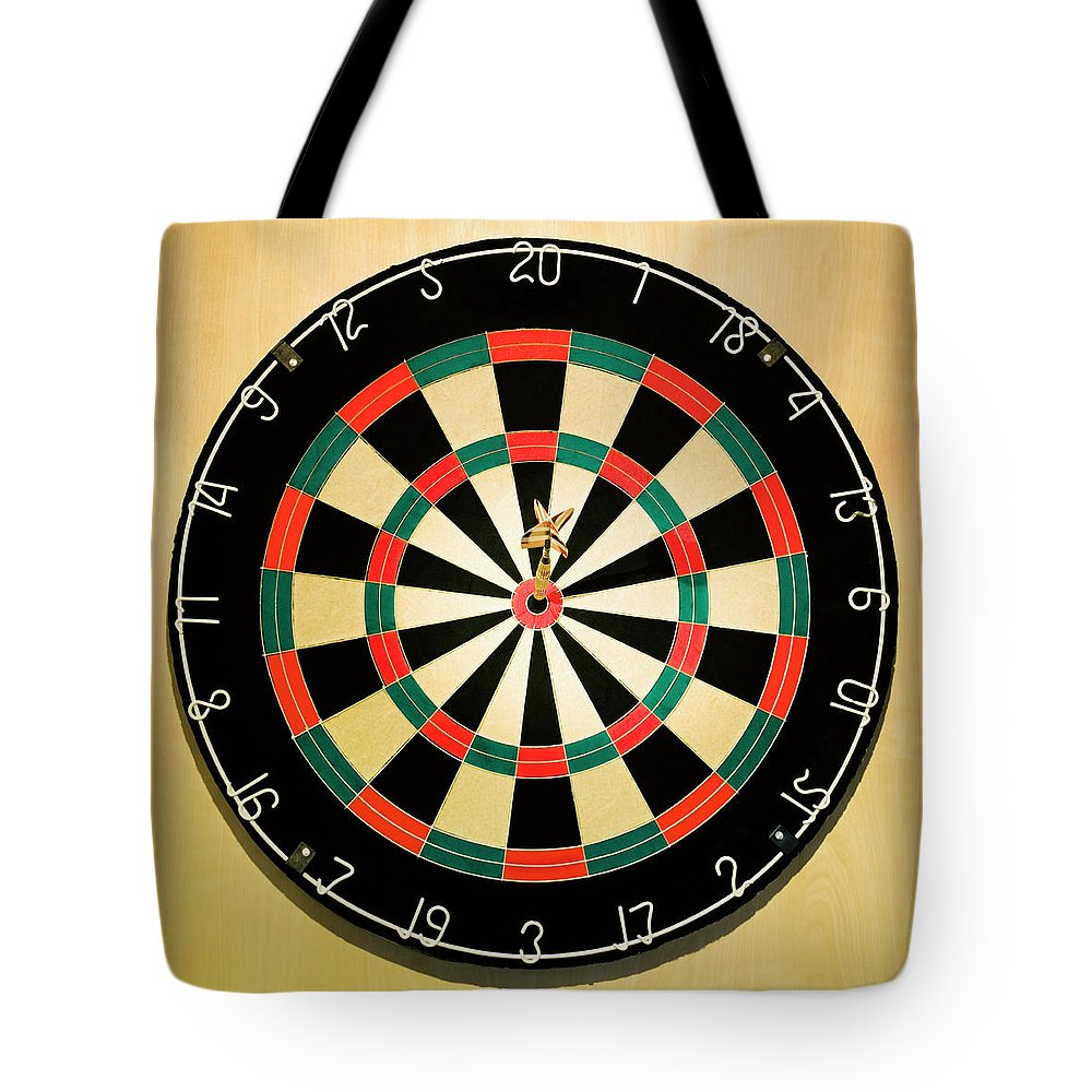 Expertise Tote Bag featuring the photograph Dart In Bulls Eye On Dart Board by Fuse