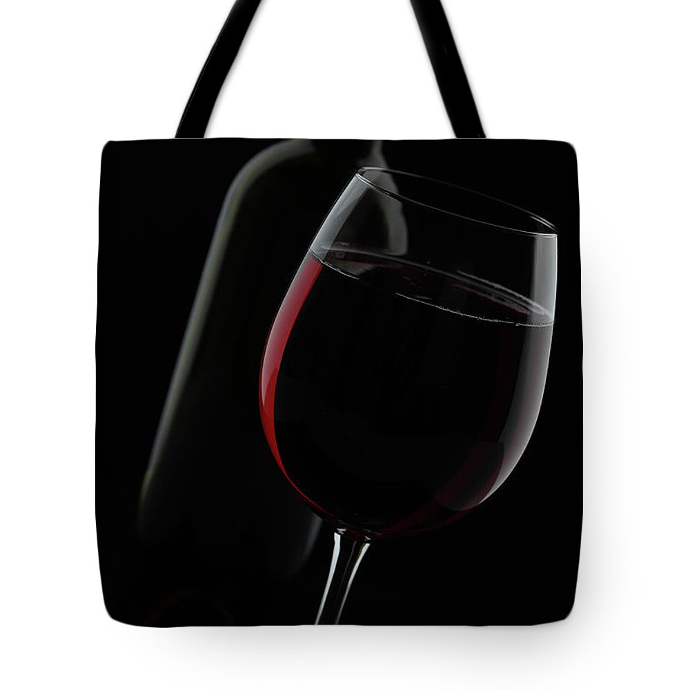 Viewpoint Tote Bag featuring the photograph Disposed Red Wine Glass And Bottle by Manuwe