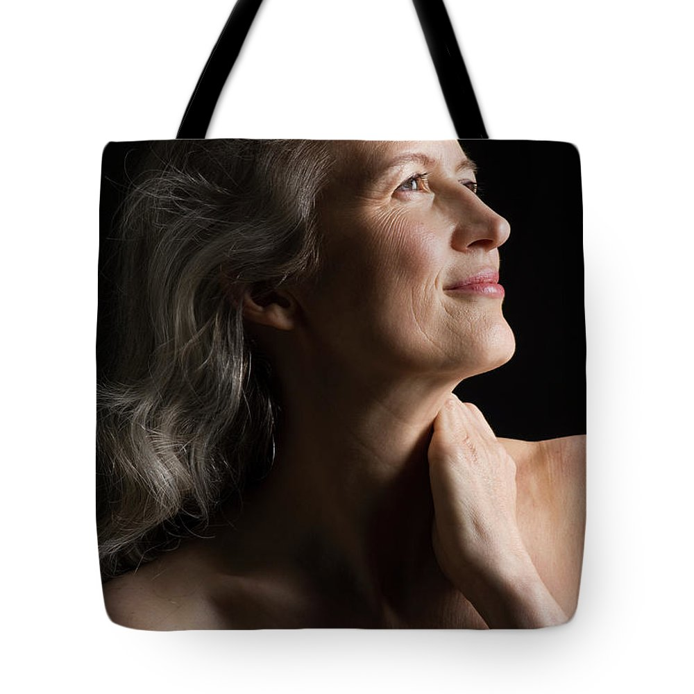 Mature Adult Tote Bag featuring the photograph Dramatic Portrait Of Mid-aged Woman by Leland Bobbe