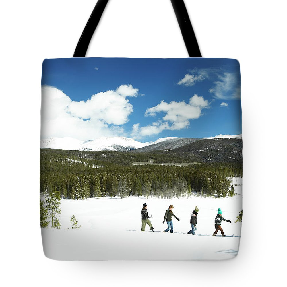 Three Quarter Length Tote Bag featuring the photograph Family Carrying Christmas Tree In Forest by Thomas Northcut