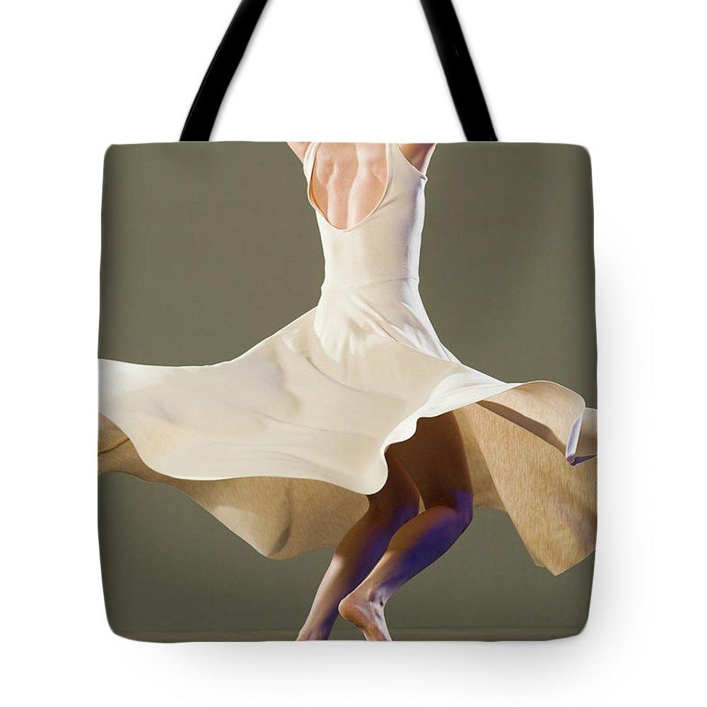 Ballet Dancer Tote Bag featuring the photograph Female Ballet Dancer Dancing by Erik Isakson