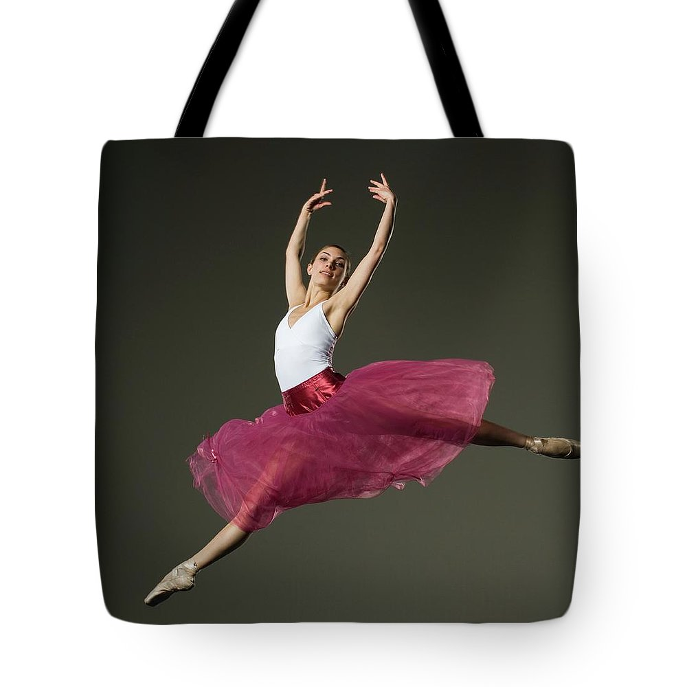 Ballet Dancer Tote Bag featuring the photograph Female Ballet Dancer Jumping by Tetra Images - Erik Isakson