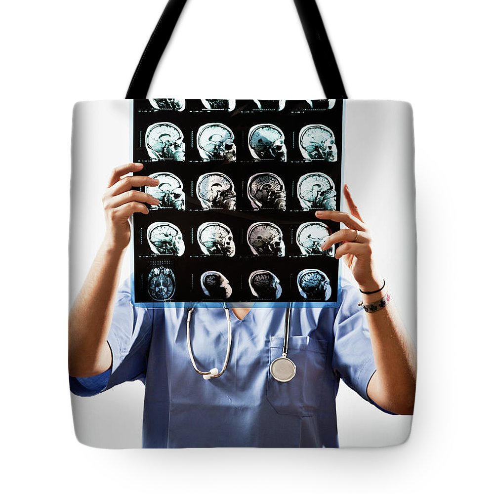 Expertise Tote Bag featuring the photograph Female Doctor Holds Up Mri In Front Of by Ron Levine